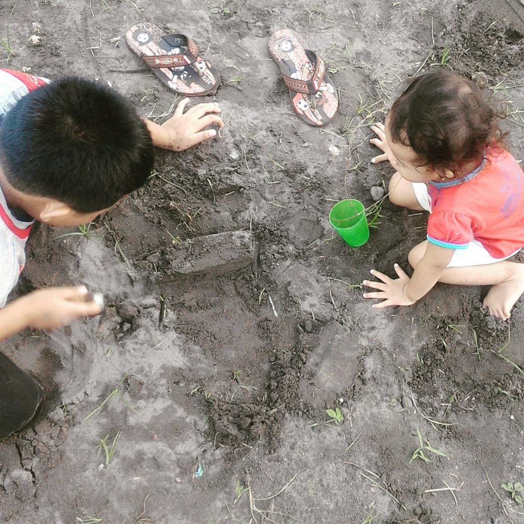Kakak adik membuat istana dari pasir dengan khidmat :)
